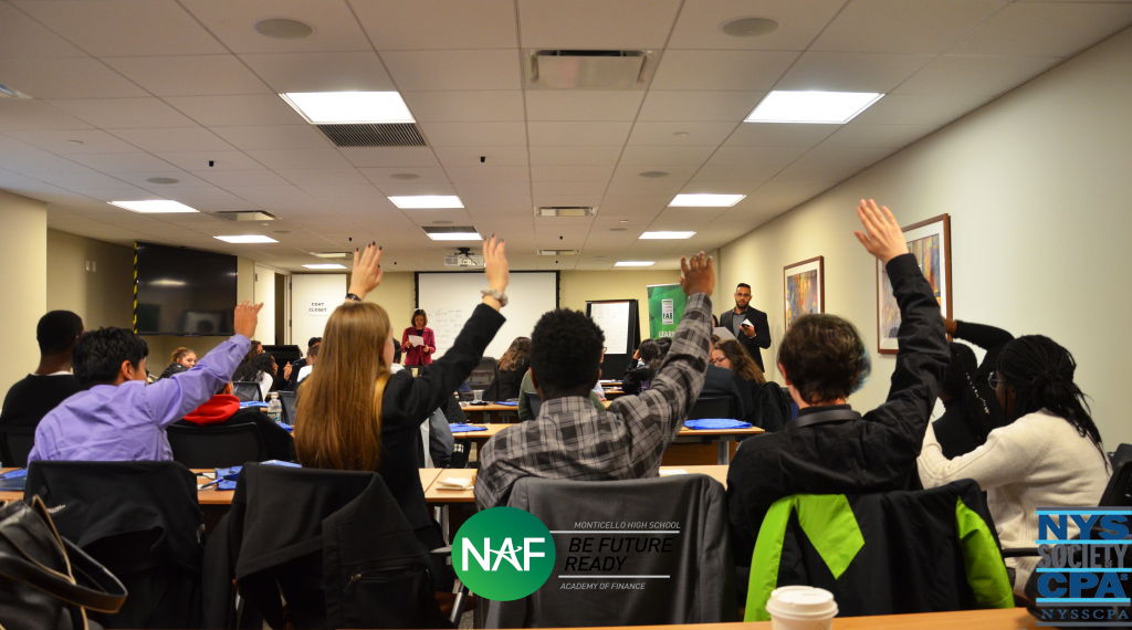 Academy of finance students raise their hands in a classroom
