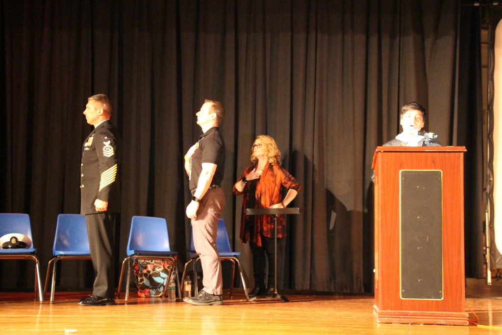 Two men and a woman have their hands over their hears for the pledge of allegiance on a stage