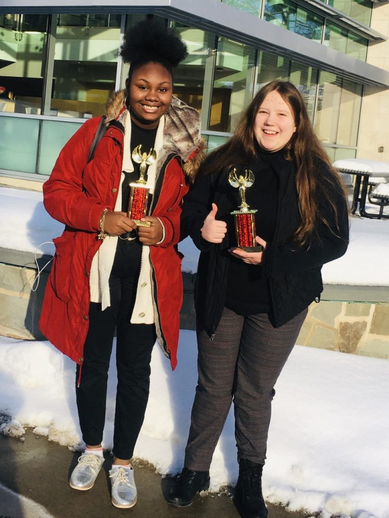 Two young women, one waring a red coat and the other a black sweater hold trophies and smile.