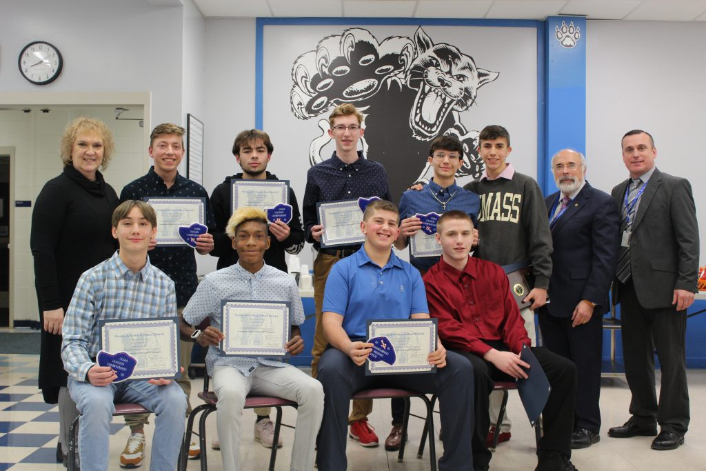 the boys cross country team is seated with their certificates