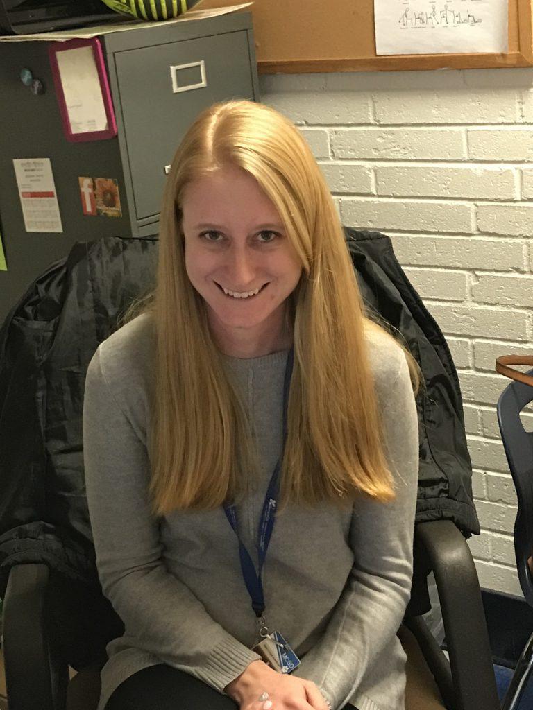 Katie Rubin smiles at her desk
