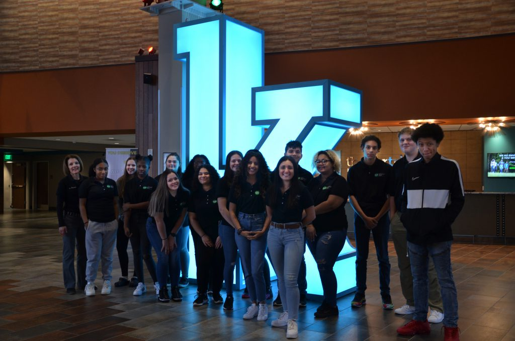 "a group of students standing in front of a large ""K"""
