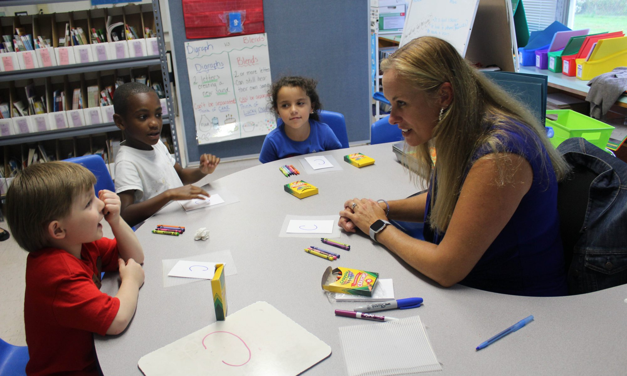 Three small students sit around a circular table. A teacher with long blond hair sits in the center. There are crayons and paper on the table.