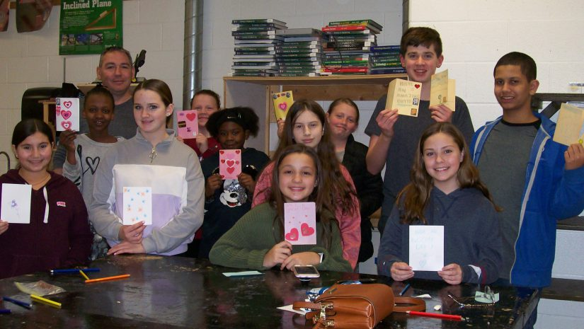 A group of 11 middle school students and one teacher stand holding up the Valentines cards they made