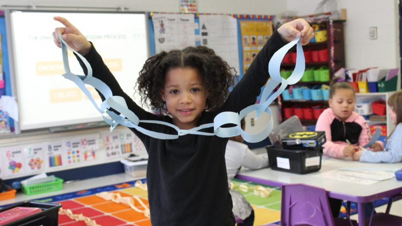 a student is holding up a paper chain she made