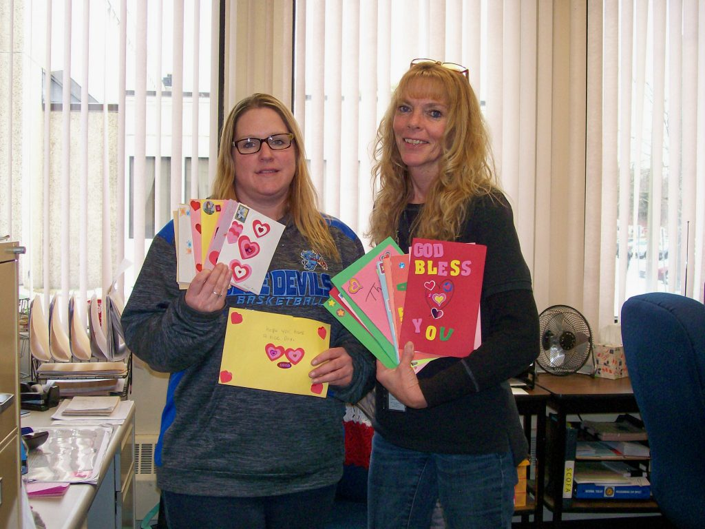 Two women with long blonde hair hold up festiva Valentine's Day cards.