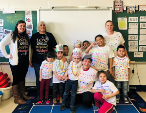Mrs. Franzone and her students are wearing 100th day t-shirts and smiling
