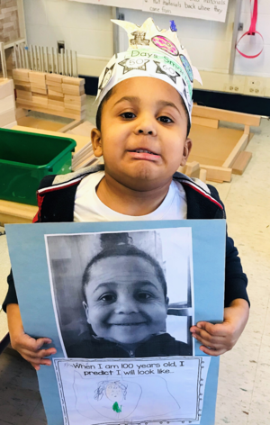 Armani Martinez is holding a piece of paper that has a photo of himself and a drawing of what he imagines he'll look like at 100 years of age. He is making a funny face.