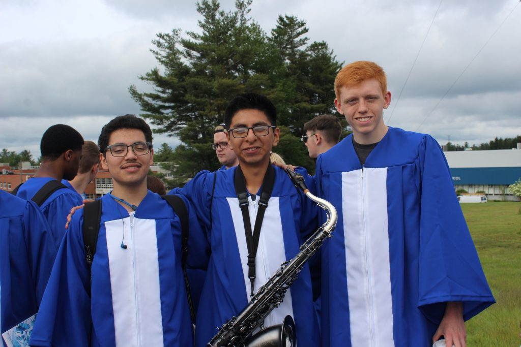 three students in graduation robes are smiling. The student in the center has a saxaphone around his neck