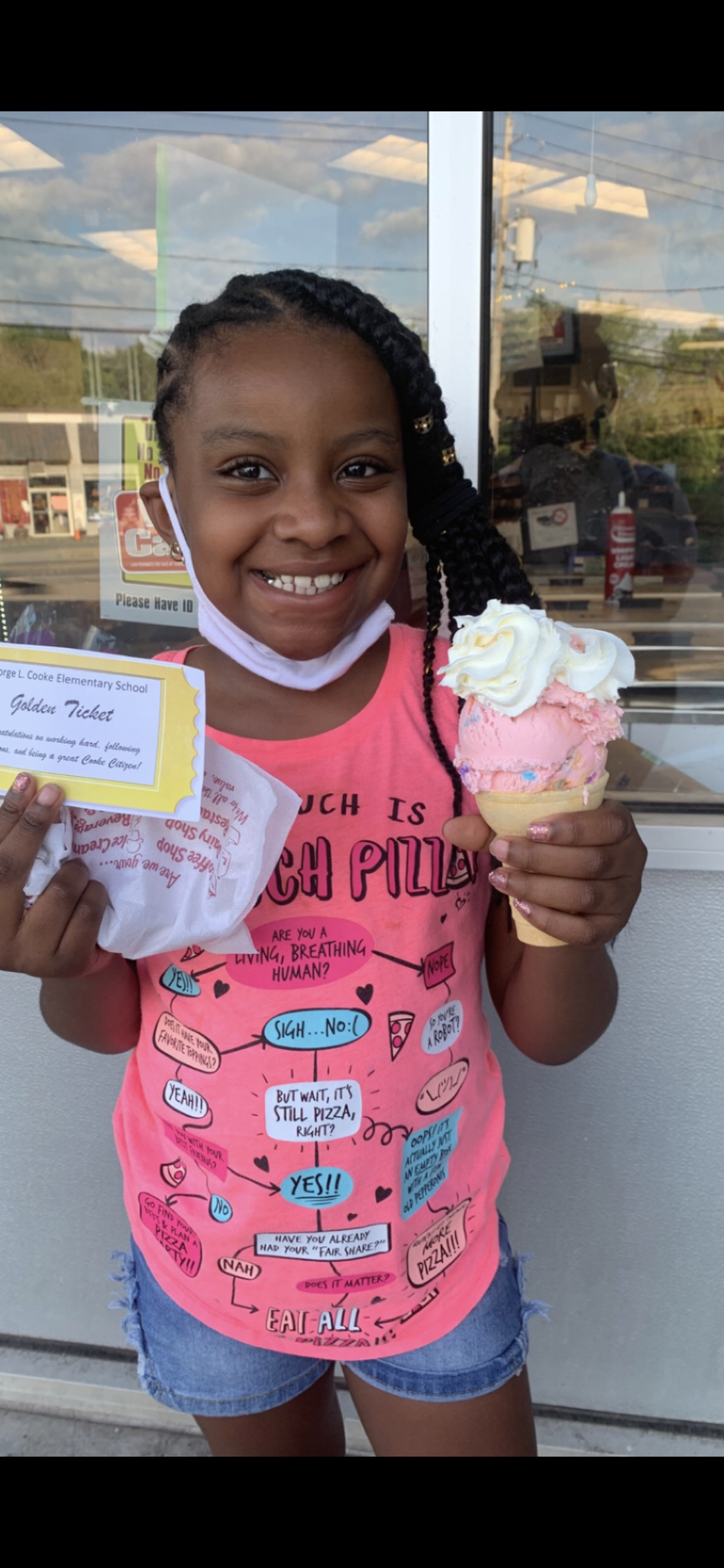 Laday, wearing a pink shirt is holding up an ice cream cone and smiling.