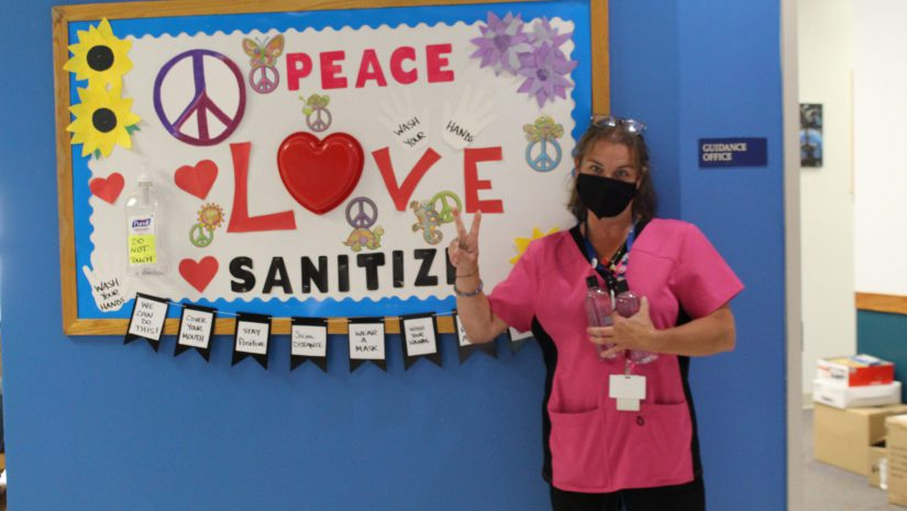 """a staff member is standing next to a bulliten board that reads """"peace love and santizier"""""""