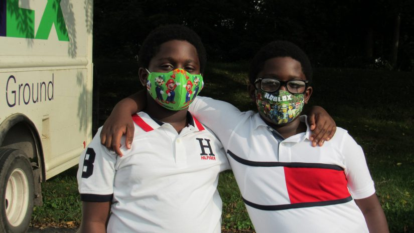 Two boys, who are brothers, wear their masks and pupt their arms around each other's shoulders