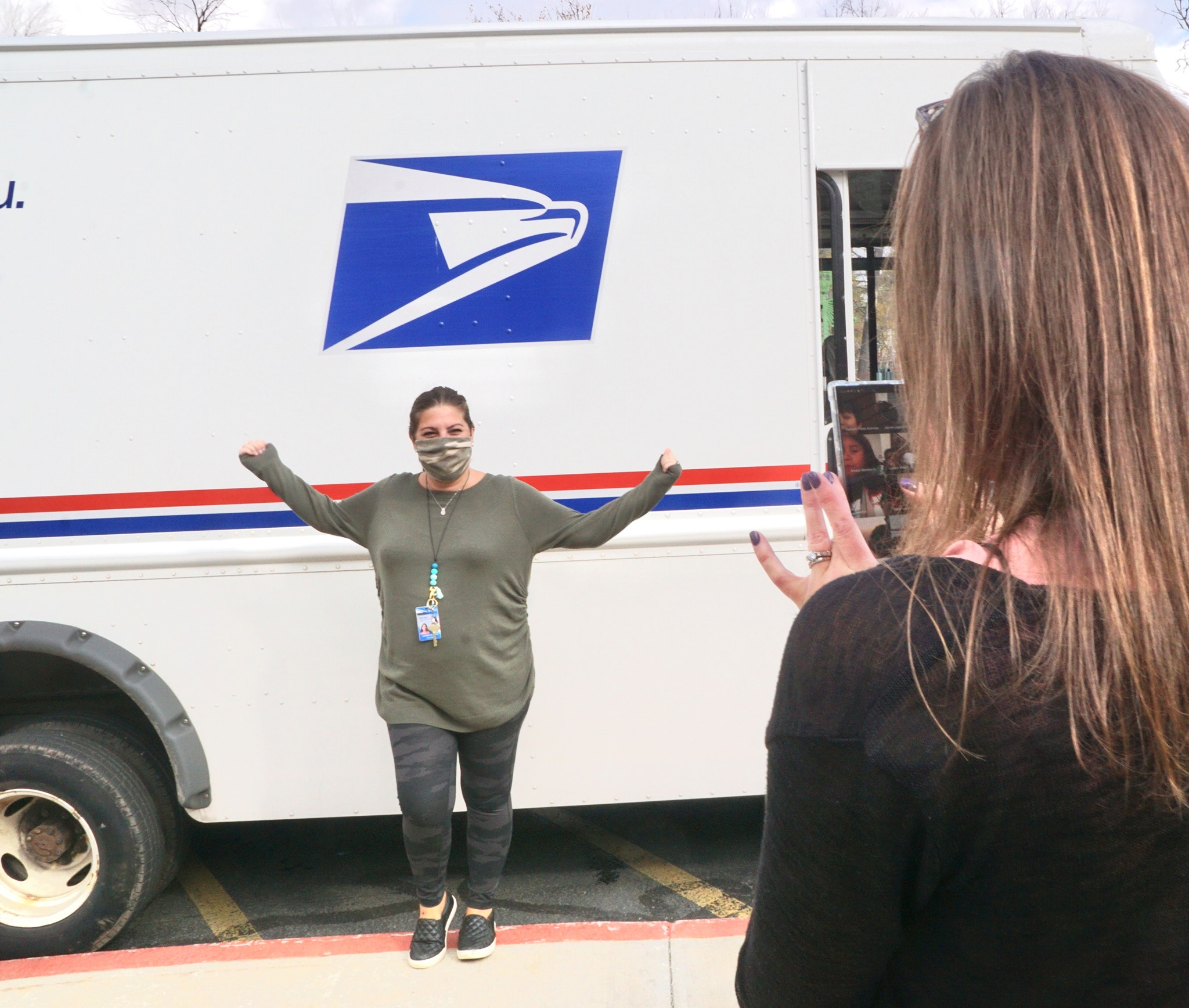 a teacher is filming a postal worker. The postal worker is standing beside a mail truck with her arms outstretched.
