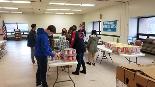 high school students begin filling white baskets with food