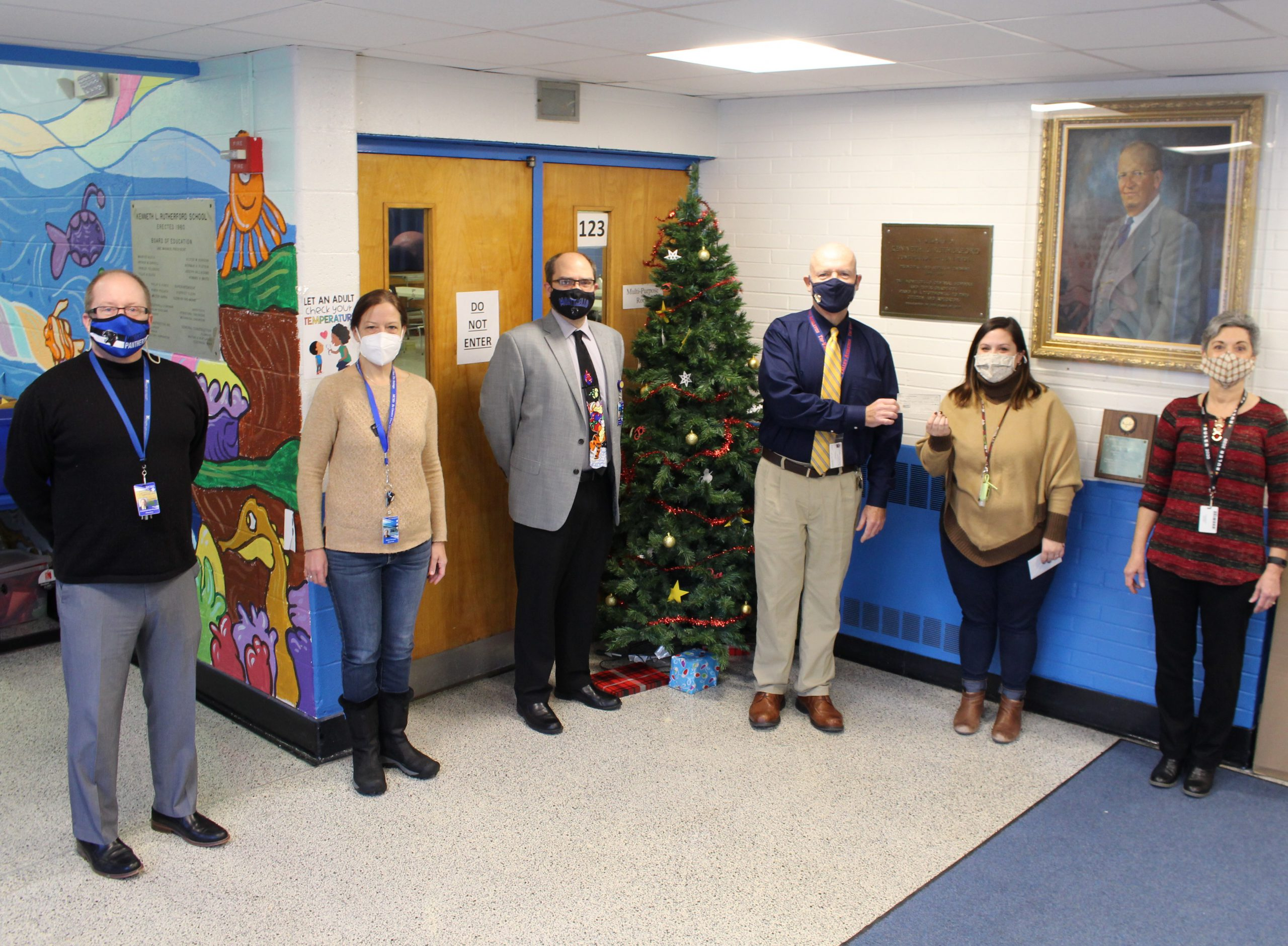 staff members are standing in the school hallway near a Christmas tree. Mike Williams is handing a check for $500 to Sarah Mootz to buy presents for students in need