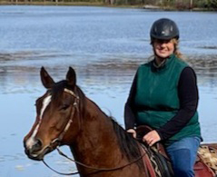 A woman wearing a riding helmet and green vest rides a horse. With water in the background.
