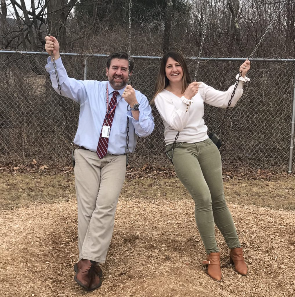Ginny Gallet and Bill Frandino are sitting on swings and smiling