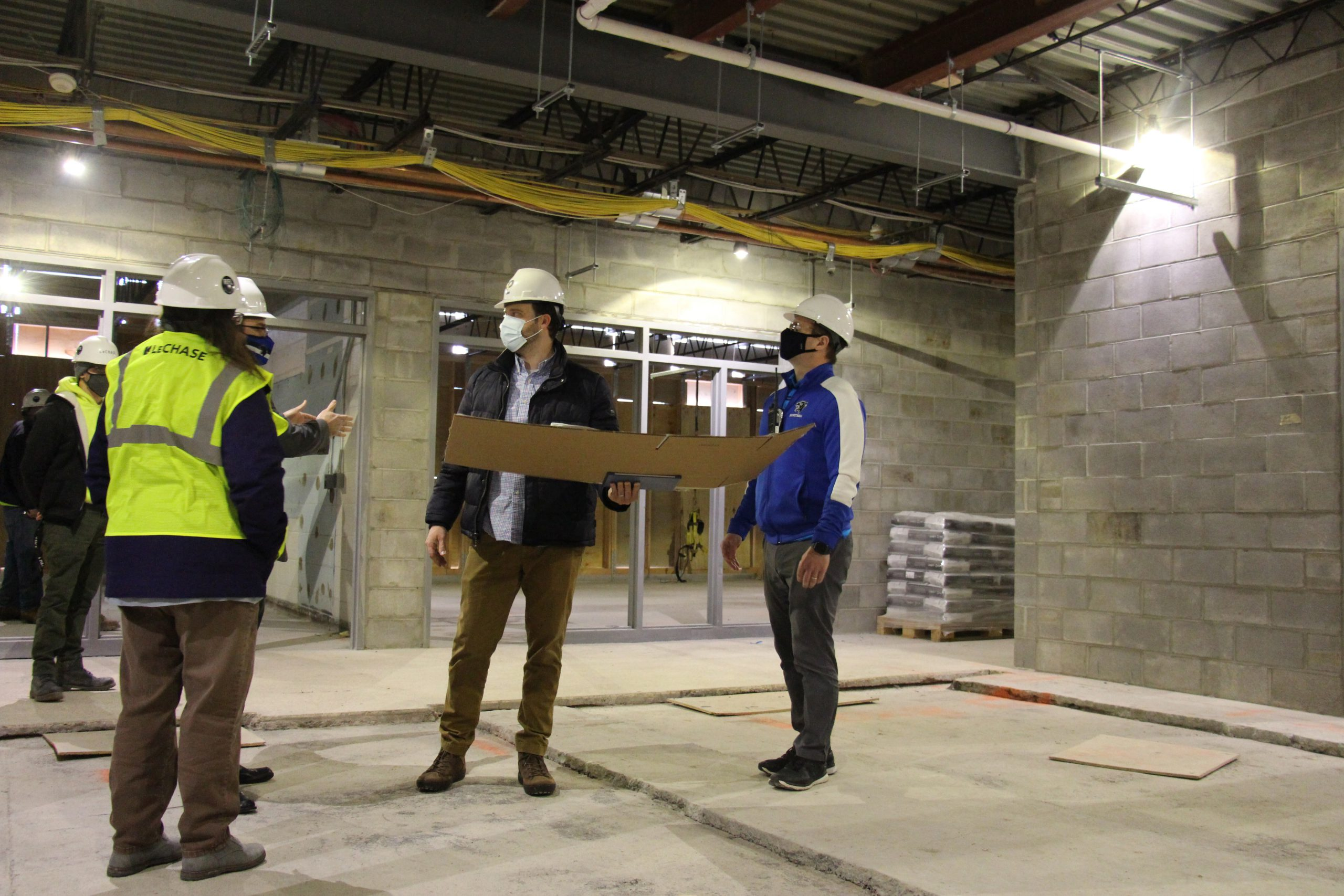 District administrators are in the building construction site and looking up