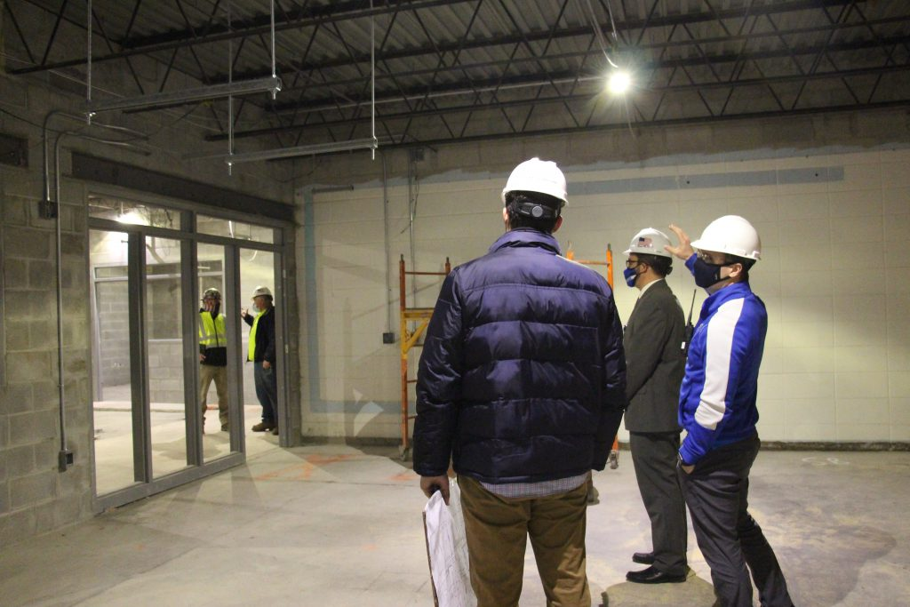 A group of people in hard hats look at the construction being done in a building.