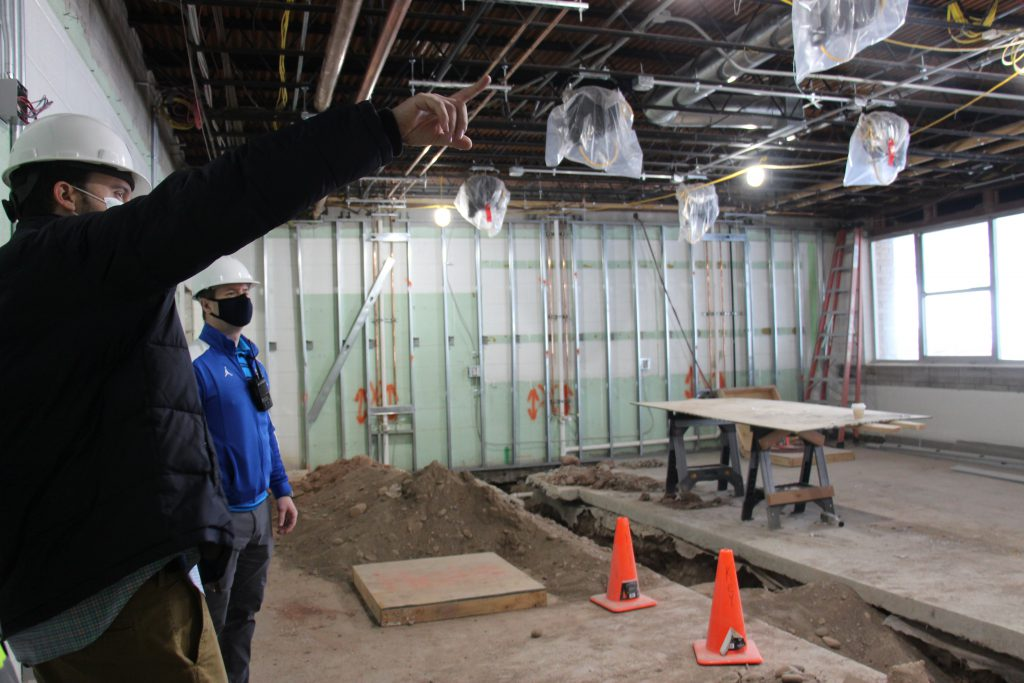 Two men look at the construction being done in one of the science labs. Two orange cones mark where a trench has been dug.
