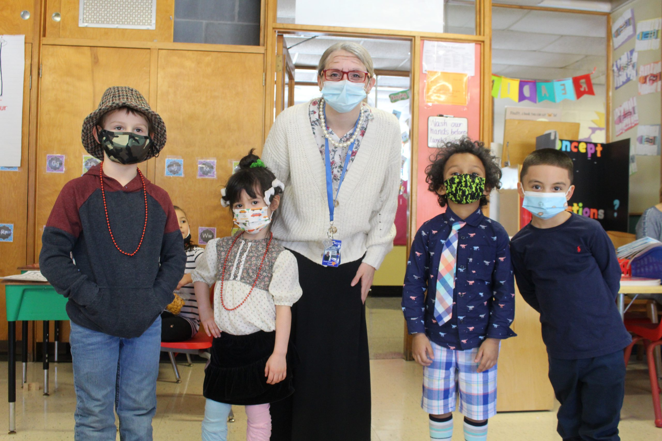 a teacher and students, all wearing centenarian costumes, are posting together and smiling