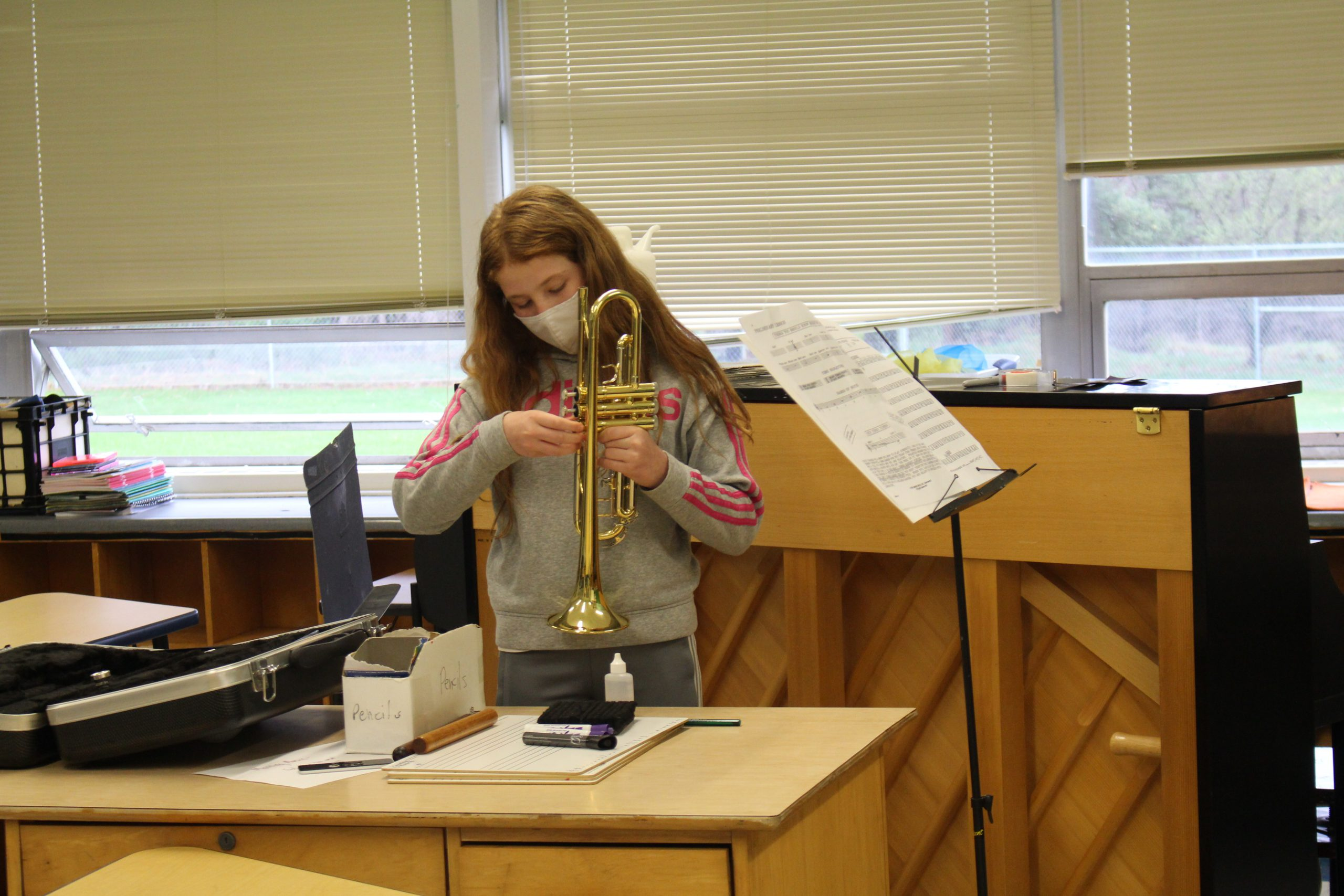 a girl is setting up her trombone