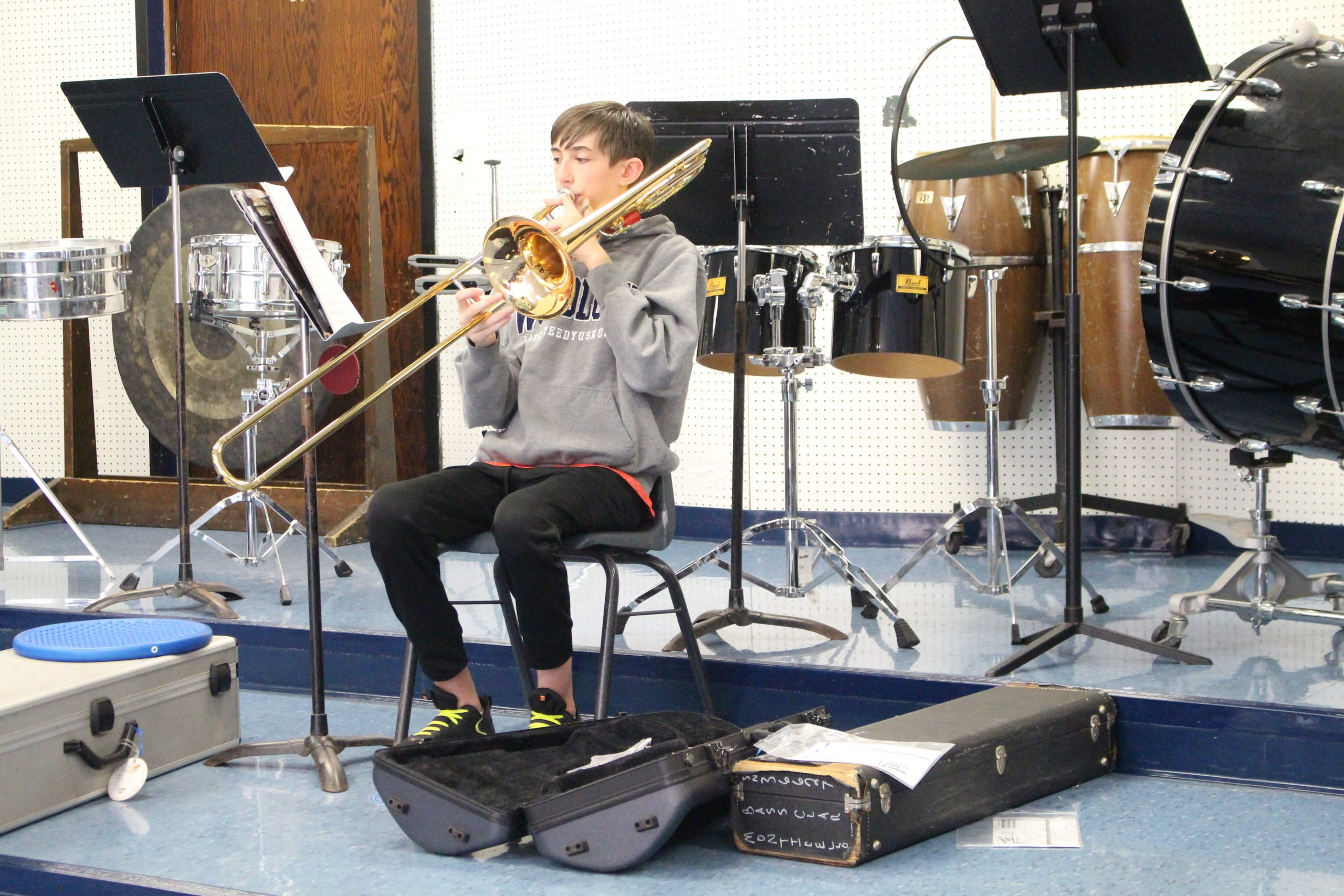 a boy is playing the trombone