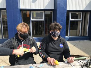 Two male high school students wearing black shirts and masks sit at a table making rockets out of green paper.