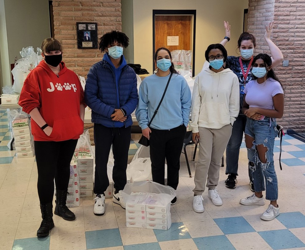 A group of six students standing in a room. All ae wearing masks.