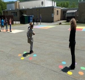 Two students standing on blacktop. At each of their feet is a circle of different colored dots - blue, red, yellow, orange, green