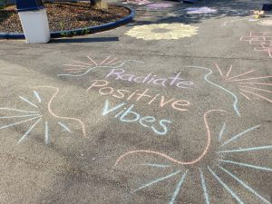Chalk on the blacktop that says Radiate Positive Vibes in different pastel colors