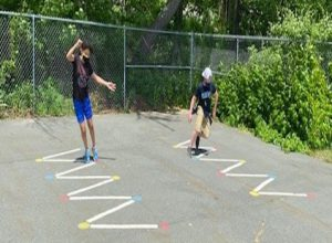 A zig zap drawn on blacktop with two older students weaving their way through it.