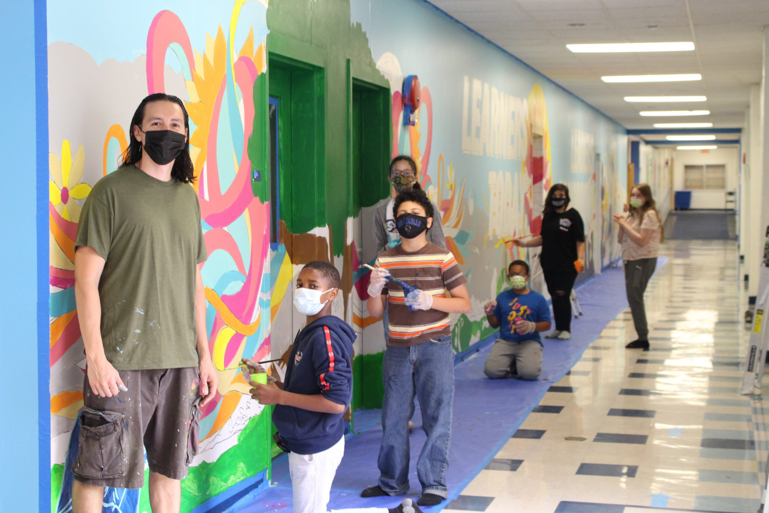 joe pimentel and student artists are standing next to the mural they created