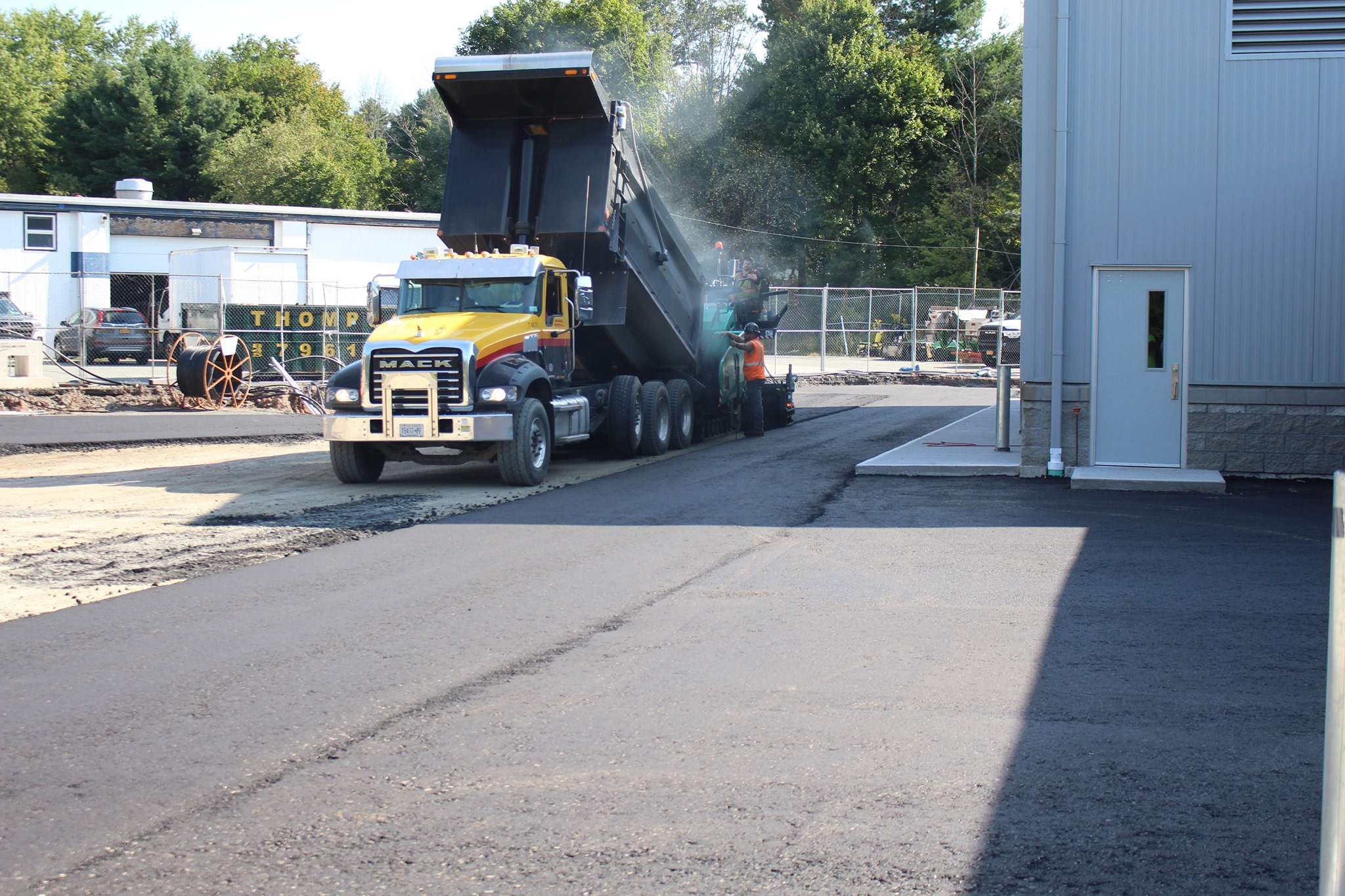 a truck is pouring blacktop outside the new transportation center
