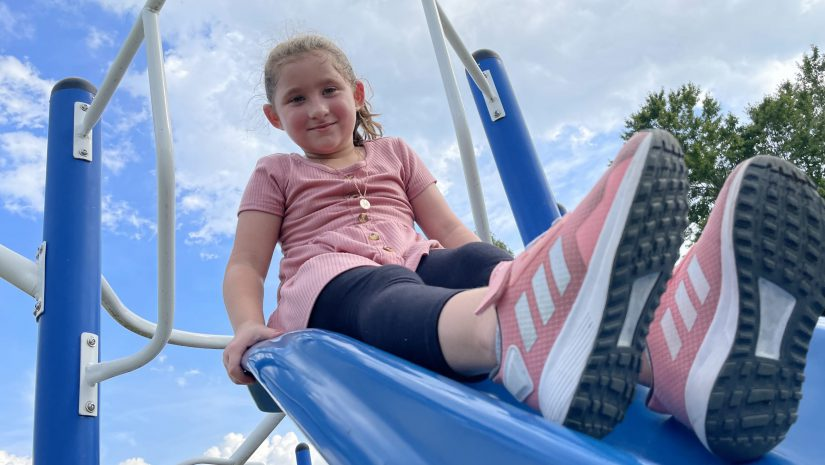 a young girl is seated at the top of a slide