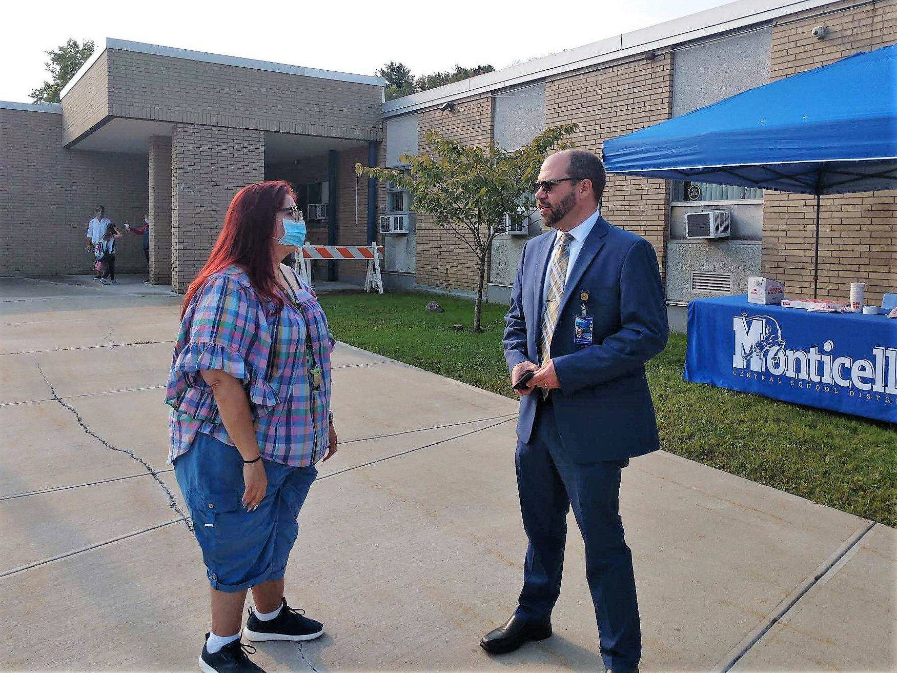 superintendent evans is outside of a school and speaking with a woman