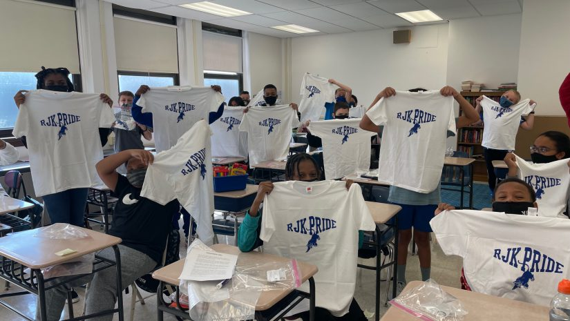 """a classroom full of students is holding up white shirts that say """"RJK pride"""" in blue letters"""